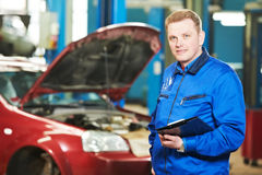 Happy mechanic technician at service station. Smiling happy mechanic technician inspector foreman with clipboard at car maintenance repair service station Stock Photography