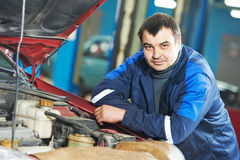 Happy mechanic technician at service station. Smiling happy mechanic technician worker at car maintenance repair service station Royalty Free Stock Images