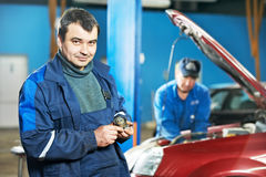 Happy mechanic technician at service station. Smiling happy mechanic technician worker at car maintenance repair service station Stock Images