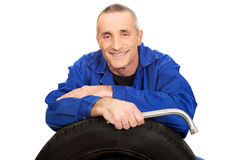Happy mechanic with a tire and wrench Royalty Free Stock Photos