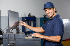 Happy Mechanic Using Computer In Repair Shop Stock Photos