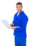 Happy mechanic using laptop on white background Royalty Free Stock Photography