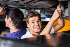 Happy Mechanic Working Under Lifted Car With Colleague Royalty Free Stock Images