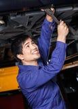 Happy Mechanic Working Underneath Car. Happy male mechanic working underneath lifted car at auto repair shop royalty free stock photo