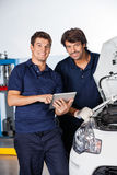Happy Mechanics With Tablet Computer Standing By Car Stock Photography