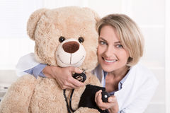 Happy medical doctor for children with a teddy bear. Royalty Free Stock Images