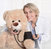Happy medical doctor for children with a teddy bear. Stock Image