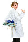 Happy medical doctor woman holding gift behind her Stock Photography