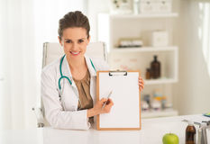 Happy medical doctor woman pointing in clipboard Royalty Free Stock Photography