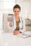 Happy medical doctor woman showing calculator Stock Images