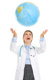 Happy medical doctor woman throws up globe Stock Image