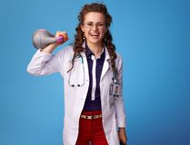 Happy medical doctor woman raising weight on blue Royalty Free Stock Image