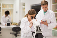 Happy medical students working with microscope Royalty Free Stock Photo