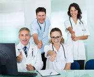 Happy medical team giving a thumbs up. Happy medical team compridsing male and female doctors smiling broadly and giving a thumbs up of success and hope Stock Images