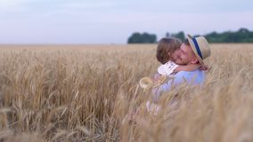 Happy meeting, little cute girl hugging happy man on wheat field during the harvest season against the blue sky stock video