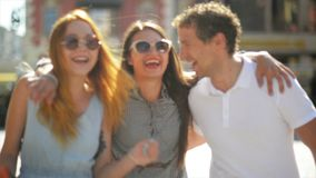 Happy meeting of three friends hugging in the street during warm summer day. Two girls wearing sunglasses and short. Dresses and handsome boy in white shirt and stock video
