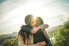 Happy meeting of two friends hugging at sunset outdoor - Pleasant moment of young sisters embracing in the wilderness stock images