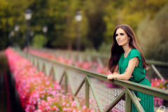 Happy Melancholic Woman on a Bridge with Flowers Stock Photography