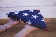 Happy Memorial Day. Girl holds a folded American flag in her hands, on a wooden background royalty free stock photo