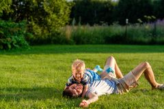 Happy father and son having fun outdoor on meadow Royalty Free Stock Image