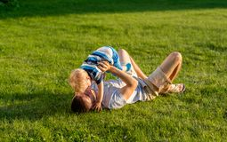 Happy father and son having fun outdoor on meadow. Happy men and child having fun outdoor on meadow.  Family lifestyle scene of father and son resting together Royalty Free Stock Images
