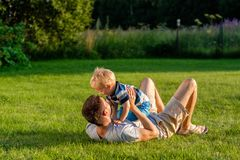 Happy father and son having fun outdoor on meadow. Happy men and child having fun outdoor on meadow. Family lifestyle scene of father and son resting together on Stock Photography