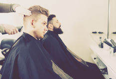 Happy men having their hair cut by hairdressers Royalty Free Stock Images