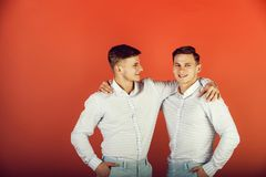 Happy men hugging. Models standing together. Family, brotherhood and friendship concept. Two brothers smiling on red background. Twins wearing blue shirts and stock images