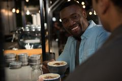 Happy man interacting while having coffee. Happy men interacting while having coffee in restaurant Royalty Free Stock Images