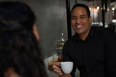 Happy man interacting with woman while having coffee Royalty Free Stock Photo