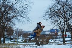 Happy man lifted his woman in beautiful evening winter park. Winter love. Stock Images
