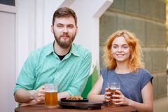 Happy goodly couple relaxing in the pub and drinking some beer. Stock Photo
