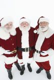 Happy Men In Santa Claus Outfits Standing Together. Portrait of three happy men in Santa Claus costumes isolated over white background Royalty Free Stock Photos