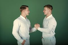 Happy men shaking hands. Two brothers smiling on green background. Twins wearing blue shirts and pants. Models standing together. Family, brotherhood and Royalty Free Stock Images