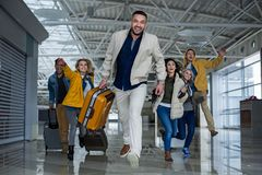 Glad companions with baggage racing at the airport. Happy men and women with cases hurrying up for boarding. They are rushing through terminal Royalty Free Stock Image
