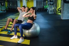 Merry couple is doing crunches on fitball indoors royalty free stock photo