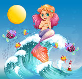 A happy mermaid above the sea waves Stock Image