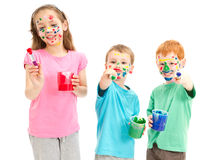 Happy messy kids with paint brushes. Messy kids holding paint brushes. Isolated on white Royalty Free Stock Photos