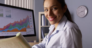 Happy Mexican businesswoman looking at camera with notes Royalty Free Stock Image