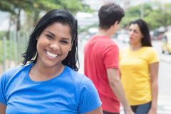 Happy mexican woman in a blue shirt with friends. Happy mexican women in a blue shirt with friends outdoor in the city Royalty Free Stock Photos