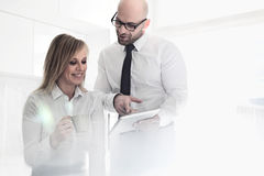 Happy mid adult business couple using tablet PC at home stock photography