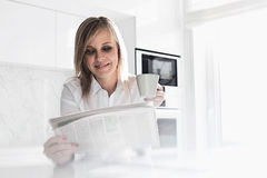 Happy mid adult businesswoman having coffee while reading newspaper at home Stock Photography