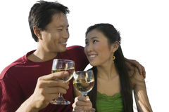 Happy mid-adult couple clinking their wineglasses against white background Stock Image