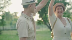 Happy mid-adult couple dancing at sunset in summer park. Portrait of positive smiling husband and wife dating outdoors
