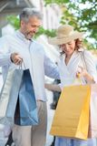 Happy mid adult couple shopping in the city center, carrying full shopping bags stock photo