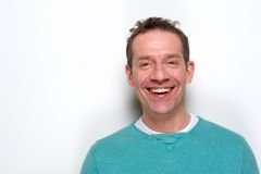 Happy mid adult man laughing. Close up portrait of a happy mid adult man laughing on white background Royalty Free Stock Photography