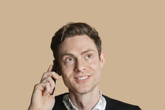 Happy mid adult man listening to mobile phone over colored background Royalty Free Stock Image