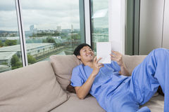 Happy mid adult man reading book while lying on sofa by window Stock Photos
