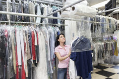 Happy mid adult woman looking up while putting clothes in plastic Stock Photo