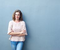 Happy mid adult woman smiling with arms crossed Royalty Free Stock Photography